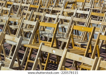 background with many wooden chairs lined - stock photo