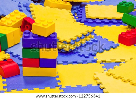 Background with multicolored plastic toy bricks and carpets