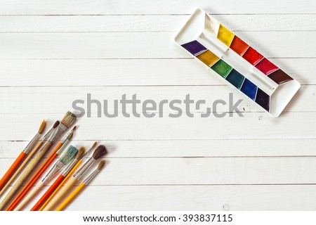 Background with paintbrushes and watercolor paints on painted wooden planks. Place for text. Top view with copy space - stock photo