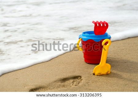 Background with red bucket with a shovel, a rake and a net on the beach with surf, foam and a wet sand - stock photo