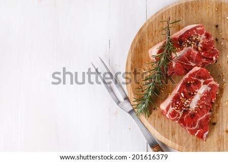 Background with red meat and rosemary over white wooden table. Top view - stock photo