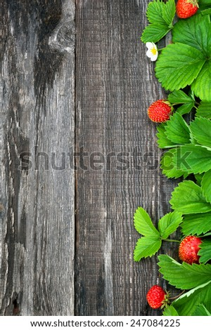 Background with ripe strawberry leaf on old wooden board  - stock photo