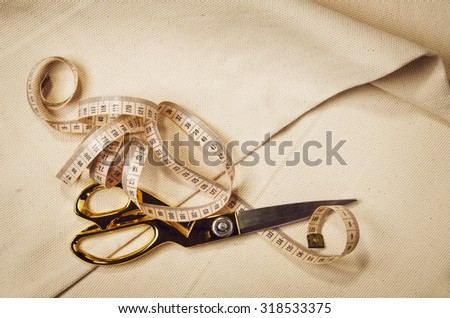 Background with sewing and knitting tools and accessories. Set for needlework placed on flax fabric. Image taken from above, top view. A lot of copyspace. - stock photo