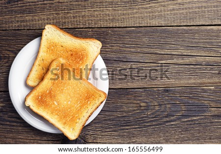 Background with slices of toast bread and old wooden table - stock photo