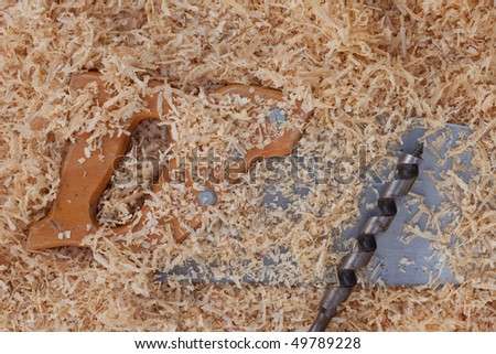 Background with softwood shavings and hand tools for woodwork: saw and drill bit.