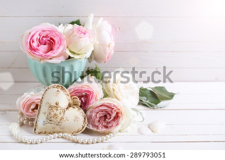 Background with sweet pink roses flowers  in ray of light on white painted wooden background against white wall. Selective focus. Place for text. - stock photo