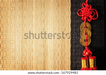 Background with three Chinese lucky coins tied with red cord on straw mat