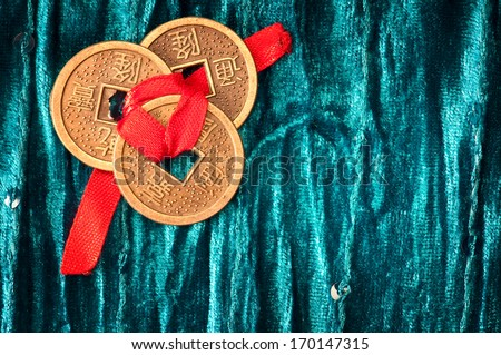 Background with three Chinese lucky coins tied with red ribbon on turquoise velvet fabric