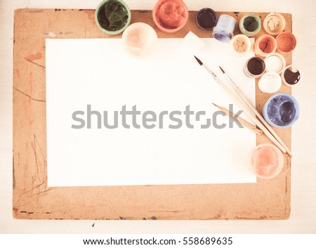 background with watercolor, brushes for artist and white blank for artwork