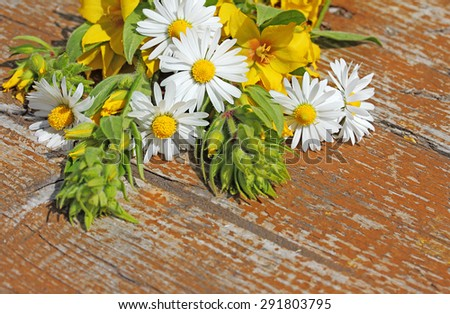 Background with wild flowers on an old table. Space for text. - stock photo