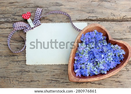 Background with wooden heart with wildflowers and card for message - stock photo