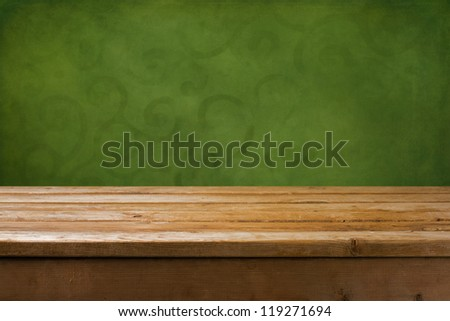 Background with wooden table and green grunge wall