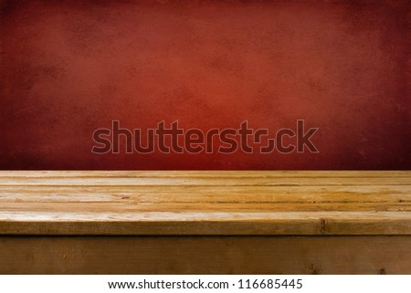 Background with wooden table and red grunge wall - stock photo