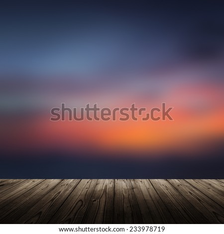 Background with wooden table and sunset at the beach - stock photo