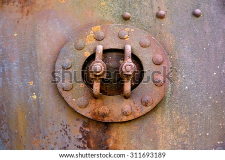Backgrounds and textures: closed hatch on rusty metal surface with riveted joints, industrial abstract - stock photo