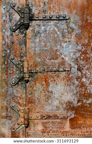 Backgrounds and textures: rusty metal door surface with riveted hinges, industrial abstract - stock photo
