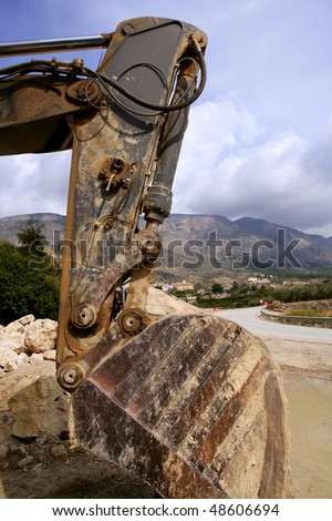 Backhoe bulldozer working hard with stones - stock photo