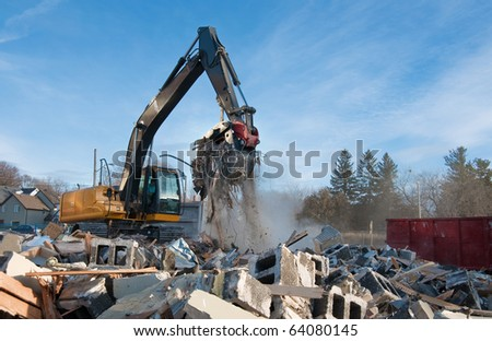 Backhoe clears rubble from building demolition - stock photo