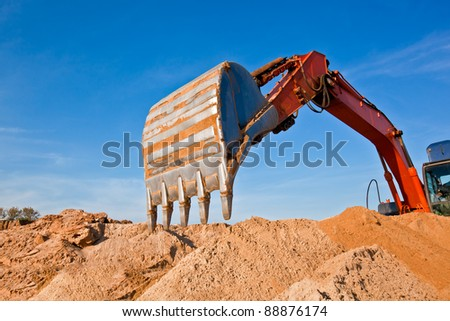 Backhoe Digging Sand at a Sand Quarry - stock photo