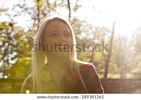 backlight beautiful blonde woman in the park or in the countryside looking up right - stock photo