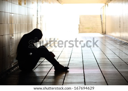 Backlight of a teenager depressed sitting inside a dirty tunnel  - stock photo