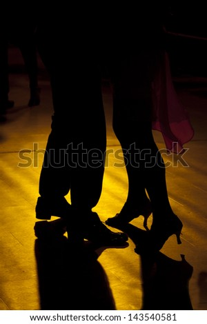Backlight of the legs of two tango dancers - stock photo