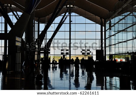 Backlight silhouette of poeple in an airport terminal - stock photo