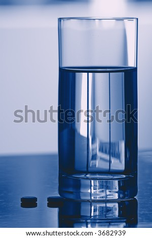 Backlighted Glass of Fresh Water and Two Pills. - stock photo