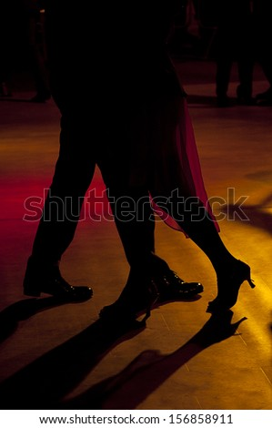 Backlighting of the legs of two tango dancers - stock photo