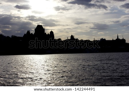 Backlit back light view of Quebec city from Saint Lawrence river in a sunny spring day - stock photo