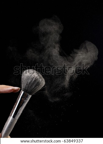 Backlit blowing to gray brush with powder making a powder cloud on black background. - stock photo
