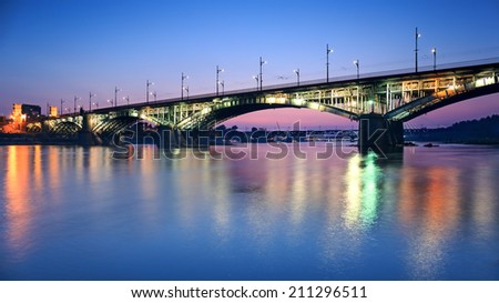 Backlit bridge at night and reflected in the water.Poniatowski bridge