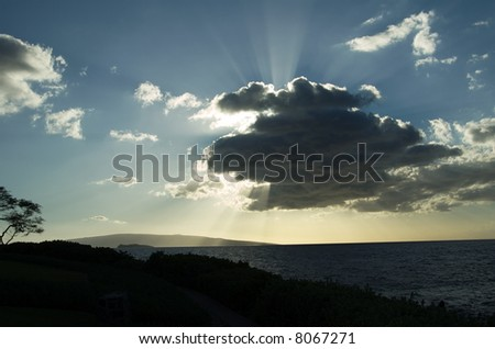 Backlit clouds with sun rays - stock photo