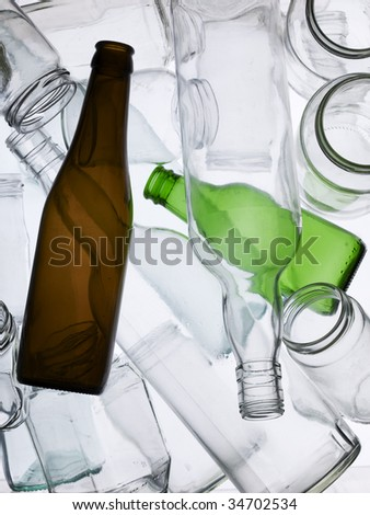 Backlit collection of glass bottles and jars - stock photo