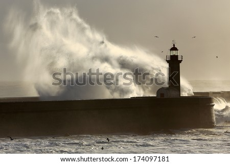 Backlit dramatic big wave over lighthouse - stock photo