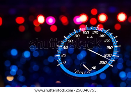 Backlit gauges of an automobile. Blue glowing meters with a white needle. Fuel, tachometer, and speedometer.
