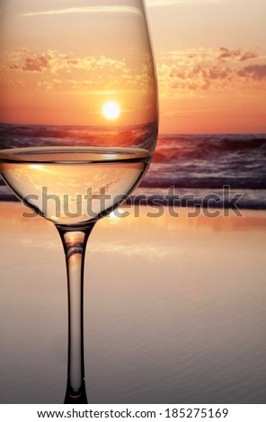 Backlit glass of water reflecting sunset - stock photo