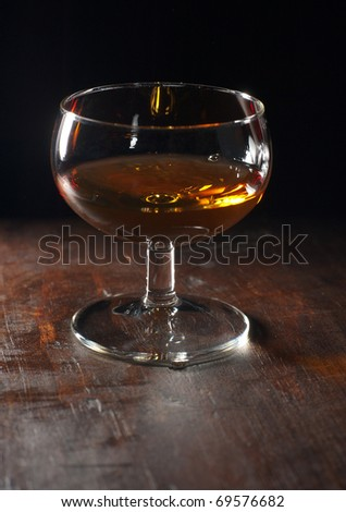 Backlit glass with liqueur on a rough wooden table