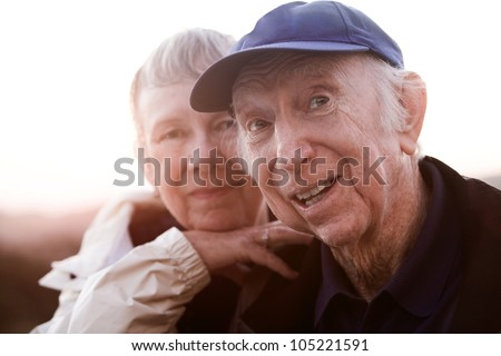 Backlit happy senior man and woman outside - stock photo