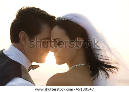 Backlit image of a newlywed couple on the beach. Horizontal shot. - stock photo