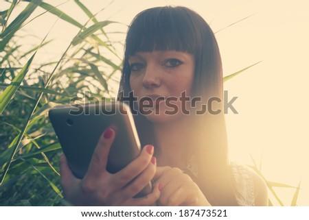 Backlit image of brunette using taplet pc outdoors in summer