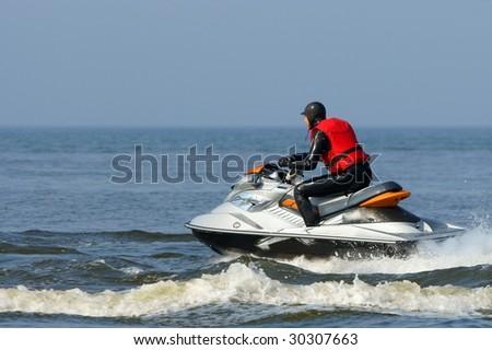 Backlit jet ski with water spray on the blue sea. Jetski in action, man on a jet-ski, making splashes. - stock photo