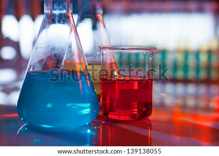 Backlit laboratory test flask containing colorful liquids. - stock photo