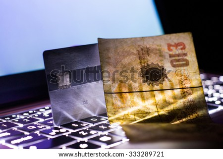 Backlit laptop keyboard with a credit card and paper money at night. Shallow DOF. - stock photo