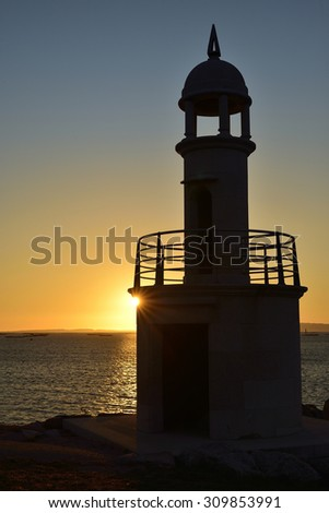 backlit lighthouse in sunset of the Rias Baixas - stock photo