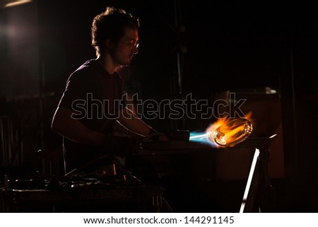 Backlit man with blowtorch shaping glass object - stock photo