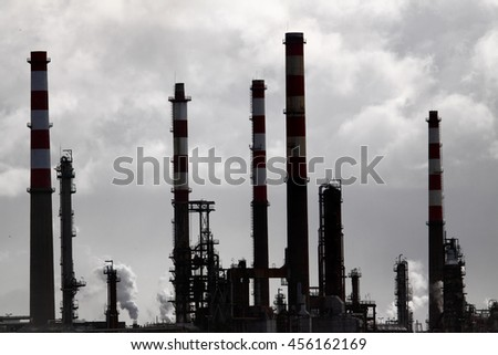 Backlit oil refinery against overcast sky