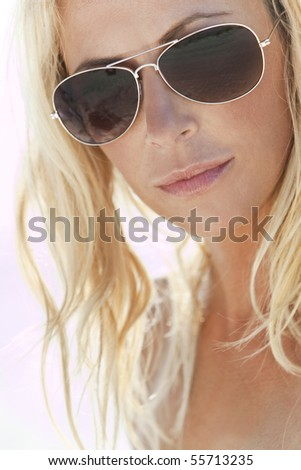 Backlit photograph of a stunningly beautiful and sexy young blond woman in aviator sunglasses