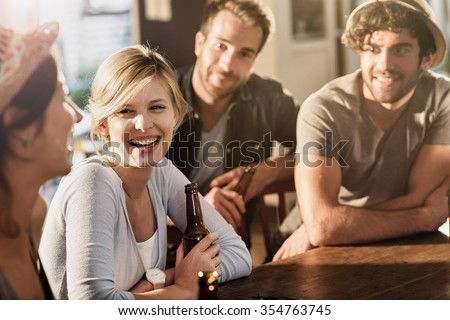 Backlit shot with flare. Friends having a drinks on a sunny evening in a bar, They are sitting at a wooden table with beers.Focus on a gorgeous blonde girl touching her bottle. - stock photo