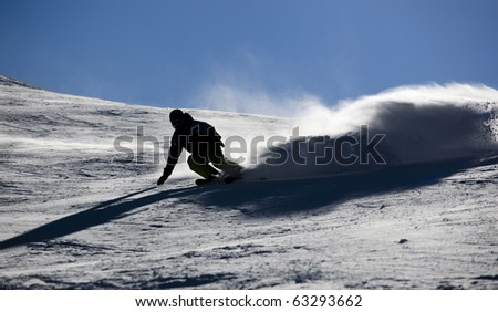 Backlit skier splashing snow powder while turning and skiing fast - stock photo